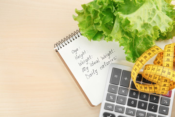 Diet concept. Measuring tape, calculator, lettuce and notebook on wooden background