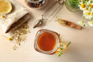 Mason jar with tasty chamomile tea on light wooden table