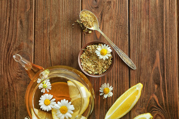 Composition with chamomile tea in glass teapot on wooden background