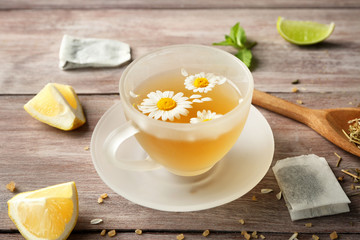 Glass cup with tasty chamomile tea on wooden background