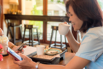 Woman drink coffee and use mobile phone in coffee shop.