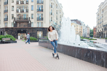 A young and attractive girl with long brown hair in a light sweater riding a scooter near the fountains in a new residential complex. Wall mural