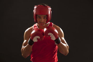 Portrait of an Indian boxer wearing gloves and head protector over black background