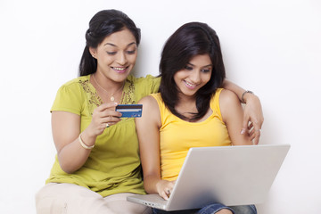 Mid adult woman and her daughter shopping online