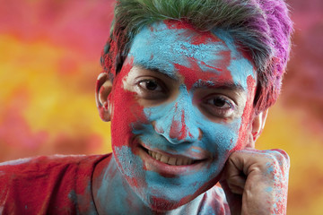 Man's face covered in holi colours