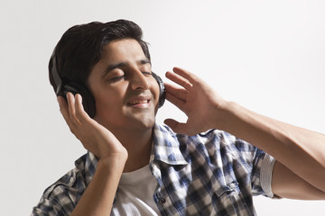 Relaxed young guy listening music over colored background
