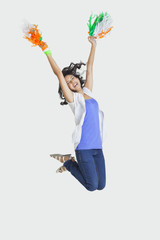 Full length of young female jumping in mid-air with Indian tricolor pom poms over white background
