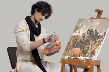 Young male artist mixing colors while painting