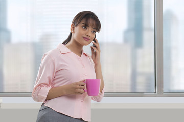 Beautiful young businesswoman with coffee cup using cell phone