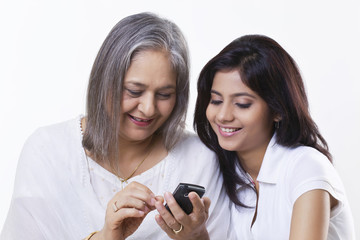 Grandmother and granddaughter looking at phone