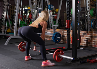 Fitness woman doing a dead lift in the gym
