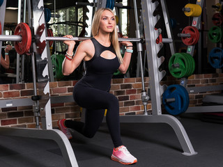 Fitness woman doing lunge squats on simulator in the gym