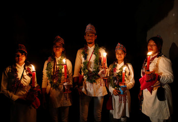 Devotees in traditional attire pose for picture as they hold candles while taking part in a parade commemorating the Neku Jatra-Mataya festival, the Festival of Lights, in Lalitpur