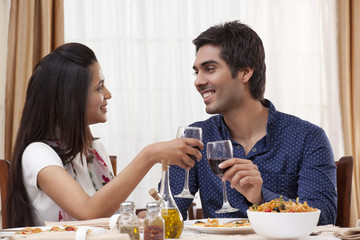 Happy young couple clinking wine glass while looking at each other at restaurant