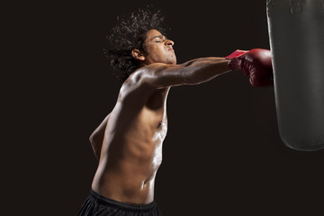 Boxer hitting punching bag aggressively