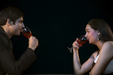 Side view of young couple drinking red wine