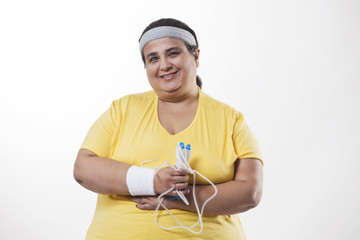Portrait of an obese female with skipping rope over white background