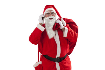 Portrait of Santa Claus talking on mobile phone while carrying sack over white background
