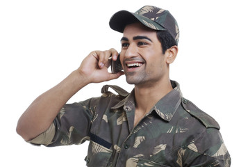Happy young soldier having conversation on cell phone