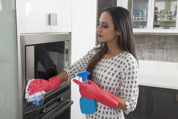 Young woman cleaning the oven