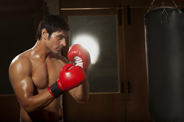 Male boxer working out with red punching bag in gym