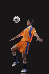 Happy male soccer player doing kick ups isolated over black background