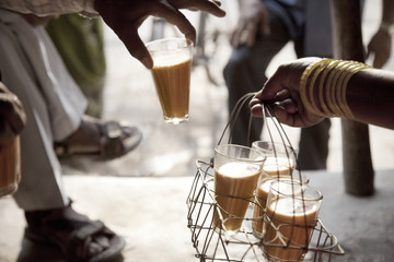 Male hand taking a glass of chai from tray held by woman