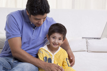 Young father assisting his son in drawing at home