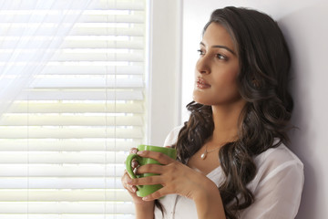 Woman with a mug of tea thinking