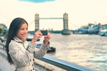 London woman tourist taking photo of Tower Bridge with mobile smart phone camera. Girl enjoying view over the River Thames, London, England, Great Britain. United Kingdom tourism concept.