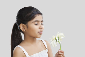 Little girl blowing on petals of a flower
