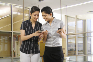 Businesswomen reading a message on a mobile phone