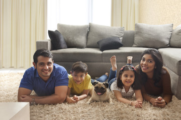 Happy family with pug posing on carpet in living room
