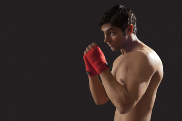 Side view of young male boxer practicing isolated over black background
