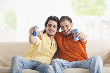 Portrait of cheerful young male friends with face painted holding out tin cans while sitting on sofa