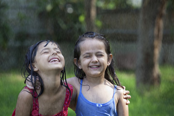 Close-up of cheerful girls enjoying in rain