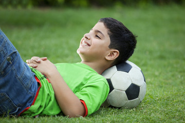 Smiling boy lying on grass with soccer ball
