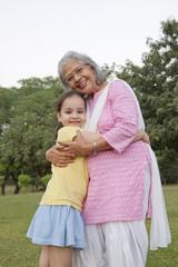 Portrait of grandmother and granddaughter hugging