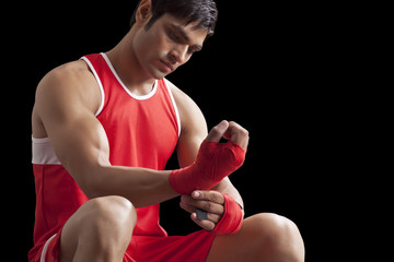 An Indian male boxer taping up hands isolated over black background