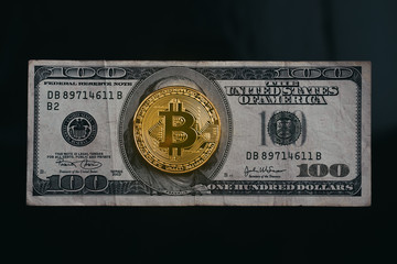 Golden bitcoin on top of old dollar bill with black  background, new currency replaces old currency  concept.