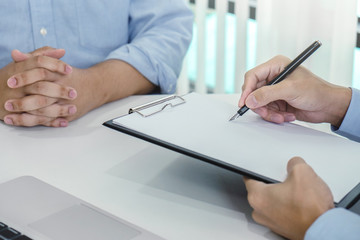 Close up of doctor filling up an history form while consulting patient and recommend treatment methods and how to rehabilitate the body