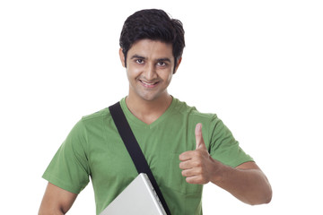 Handsome university student giving thumbs up over white background