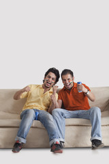 Portrait of excited young male friends with face painted cheering while sitting on sofa at home