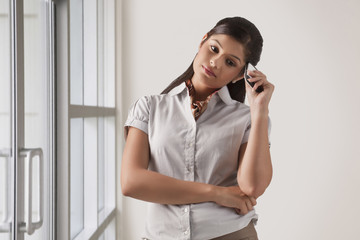 Young businesswoman in deep thought with mobile phone