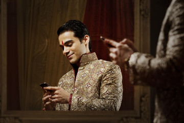 Groom reading an sms on a mobile phone
