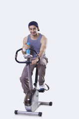 Portrait of a young man exercising while holding water bottle over white background
