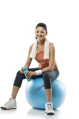 Portrait of young woman sitting on a fitness ball after workout over white background