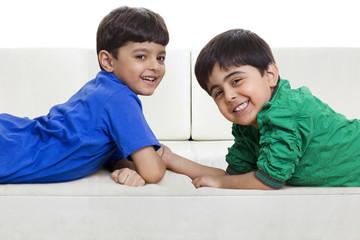 Cute smiling boys lying on sofa