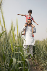 Low angle view of a happy father carrying son on shoulders