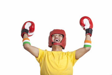 Cheerful young male boxer looking up with hands raised over white background
